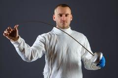 Clôture de l'athlète posant avec une épée ou une épée sur le fond gris Image stock