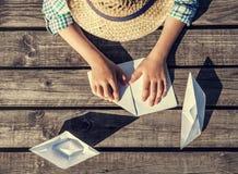 Clôturez vers le haut des mains de garçon d'image faire les bateaux de papier Photo stock