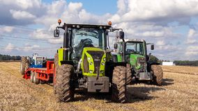 A Claas 630 tractor pulling a trailer to load vintage tractor. A new claas tractor pulling a low loader with a vintage old tractor and fendt parked at the side Stock Images
