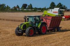 Claas traktor med en kornsläp och en Claas skördearbetare på ett kornfält fotografering för bildbyråer