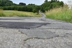 Clad bad asphalt road in the countryside. Road Royalty Free Stock Image