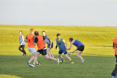 Claddagh, Galway, Ireland june 2017, friends playing touch rugby. In the free public south park fields, a girl executing a pass Royalty Free Stock Photography