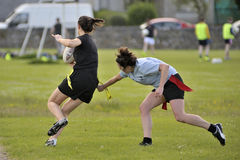 Claddagh, Galway, Ireland june 2017, friends playing touch rugby. In the free public south park fields, girl taking the strip of the other team girl who have Stock Image