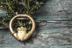Claddagh and holly branches. Irish symbol of love, friendship and loyalty in old wooden background royalty free stock photography