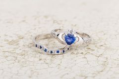 Claddagh ring with blue topaz on stone background stock photos