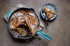 Clafoutis asados de la manzana (torta francesa de las natillas) en cacerola del arrabio  fotos de archivo