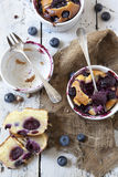 Clafoutis cakes with blueberries and cherries on ceramic ramekins on rustic white vintage background Stock Photography