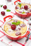 Clafoutis with cherries in red ramekin Stock Image