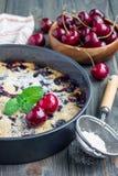 Clafoutis med körsbäret i bakningmaträtten, lodlinje arkivbilder