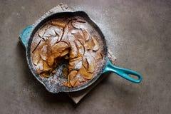 Clafoutis rôtis de pomme (gâteau français de crème anglaise) dans la casserole de fonte photographie stock