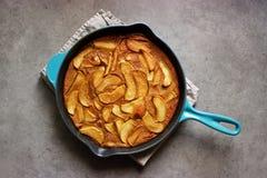 Clafoutis rôtis de pomme (gâteau français de crème anglaise) dans la casserole de fonte images stock