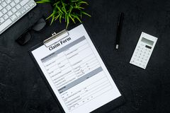 Claim form to fill out on black desk top view royalty free stock image