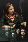 Clairvoyant. Magic woman with smoking twigs on a black background Royalty Free Stock Photos