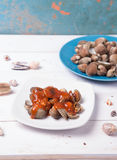 Clam with shell on a blue plate on a white wood background with chilli and tomato sauce. On wood base Stock Photo