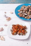 Clam with shell on a blue plate on a white wood background with chilli and tomato sauce. On wood base Royalty Free Stock Images