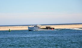 Clam  Boat Returns to Harbor. Clam Boat off Cape Cod Beach Inlet Royalty Free Stock Photos