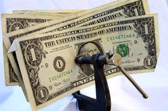 Clamp on the Dollar. American Currency squeezed by a steel clamp Stock Photo