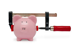 Clamp holding a piggy bank on white background Stock Images