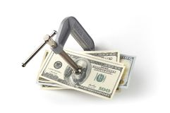 Clamp squeezing money. C-clamp squeezing 100 dollar bills on a white background royalty free stock photo