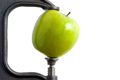 Clamped Apple. Image of a green apple squeezed in a clamp Royalty Free Stock Images