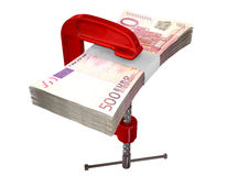 Clamped Euro Notes. A red clamp clamping down on a bundle of five hundred euro notes on an isolated studio background Royalty Free Stock Images