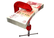 Clamped Pound Notes. A red clamp clamping down on a bundle of one hundred pound notes on an isolated studio background Stock Photography