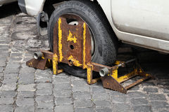 Clamped wheel. Clamped car wheel in Rome, Italy. Parking offence punished Royalty Free Stock Images