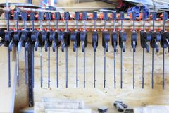Clamps mounted on the wall. Clamps attached to wood in the wokshop royalty free stock photo