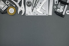 Clamps, vernier caliper, ruler, drill and other tools on grey ba Stock Photo