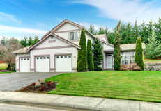 Clapboard siding house. Curb appeal. Two story clapboard siding house with garage, drive way, green lawn and fir trees Royalty Free Stock Photography