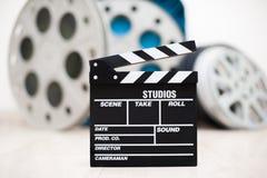 Clapper κινηματογράφων κινηματογράφηση σε πρώτο πλάνο πινάκων με τα εξέλικτρα κινηματογράφων στο υπόβαθρο Στοκ Φωτογραφίες