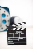 Clapper κινηματογράφων κινηματογράφηση σε πρώτο πλάνο πινάκων με τα εξέλικτρα κινηματογράφων στο υπόβαθρο Στοκ Εικόνες
