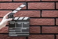 Clapper πιάτα, χέρια γυναικών ` s και clapper κινηματογράφων με ένα τούβλο β Στοκ εικόνες με δικαίωμα ελεύθερης χρήσης