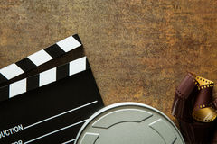 Clapper board with film reel. Clapper board with film reel on rusty background. Top view Stock Images