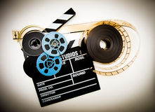 Clapper board and film reels vintage color effect. Clapper board with 8mm and 35mm film reels in white background and vintage color effect stock photography