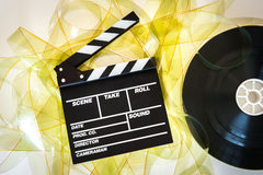 Clapper board with 35mm film yellow frames and movie reel. Empty yellow 35 mm film unrolled with clapper board and cinema movie reel on neutral background stock photo