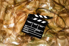 Clapper board on 35mm unrolled movie filmstrip blank frames carp Stock Photos