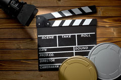 Clapper board with movie light and film reels on wooden table Stock Image