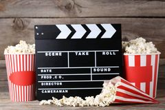 Clapper board with popcorn. In striped buckets on wooden table royalty free stock photos