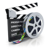 Clapper board and reel with filmstrip. Cinema, movie, film and video media industry concept: clapper board and reel with filmstrip with colorful pictures Stock Photography