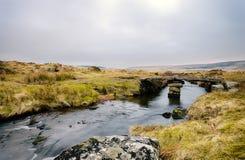 Winters Evening on Dartmoor. A clapper bridge over Walla Brook at Scorhill on Dartmoor National Park Royalty Free Stock Photos