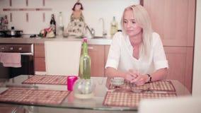 Clapper deska klascze przed ślicznym blondynki dziewczyny obsiadaniem przy stołem w kuchni zbiory wideo