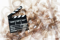 Clapper on 35mm movie unrolled filmstrip texture. White background vintage color effect royalty free stock images