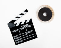 Clapper and 35mm reel isolated. On white background royalty free stock photos