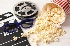 Clapper, popcorn, rulle och exponeringsglas på trätabellen royaltyfri foto