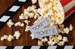 Clapper, spillt popcorn och filmbiljetter på en bakgrund av bräden royaltyfri bild