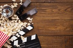 Clapperboard、影片轴和玉米花在木背景,顶视图 免版税库存图片