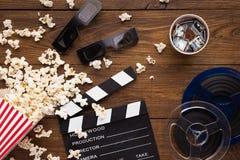 Clapperboard、影片轴和玉米花在木背景,顶视图 库存照片