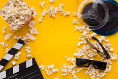 Clapperboard、3D玻璃和玉米花在黄色背景 库存照片