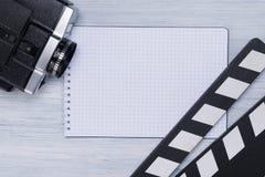 Clapperboard, a câmara de vídeo e o caderno para registros estão no fundo claro da tabela do diretor imagens de stock royalty free